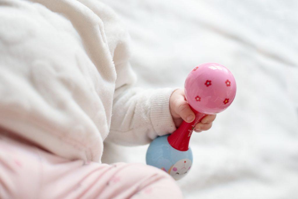 Das Baby lernt das Spüren mit den Händen.